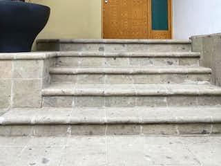 Una persona sentada en los escalones delante de un edificio en SANTÍSIMO