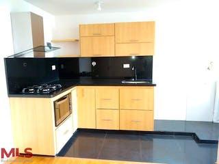 Una cocina con armarios de madera y electrodomésticos negros en Mirador de la Hacienda (San Antionio Prado - Urbano)