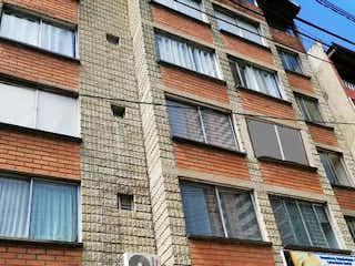 Un edificio de ladrillo con un reloj en el lado en Casa en Venta ROBLEDO