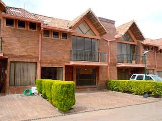 Un gran edificio de ladrillo con un banco verde en Vendo casa Chía Conjunto Cerrado entre Pradilla y Chilacos, Chía