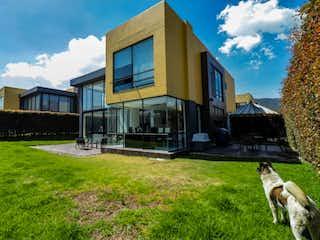 Un perro está sentado delante de una casa en CASA EN COTA