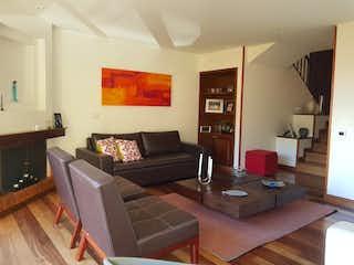 Una sala de estar llena de muebles y una televisión de pantalla plana en Casa En Venta En Bogota Bosque De Pinos