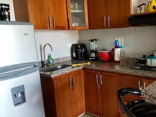 Una cocina con una estufa de nevera y fregadero en venta Apartamento Sabaneta, Antioquia