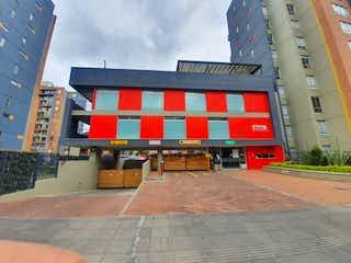 Un edificio de ladrillo rojo con un banco rojo en VENTA APARTAMENTO BOGOTA CIUDAD ALSACIA