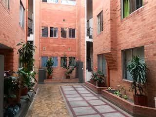 Un edificio de ladrillo alto con una planta en maceta en Vendo Apartamento Las Villas Bogotá