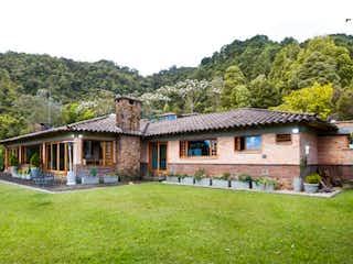 Una casa que tiene un banco de madera en ella en Espectacular Casa campestre en el Alto del Escobero