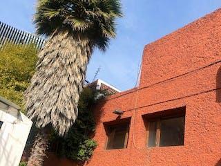 Un edificio de ladrillo alto con un árbol grande en Casa en Condominio para remodelar, Tlacopac / Alvaro Obregon