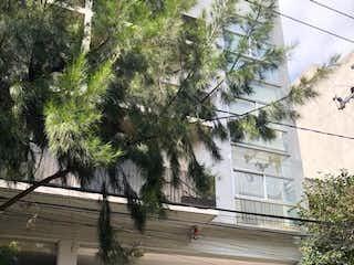 Un edificio que tiene un árbol a su lado en VENTA DEPARTAMENTO EN LA COLONIA NÁPOLES