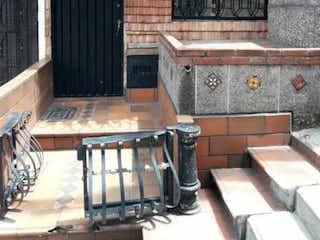 Un banco de madera sentado delante de un edificio en SE VENDE CASA GUAYABAL CASA LINDA