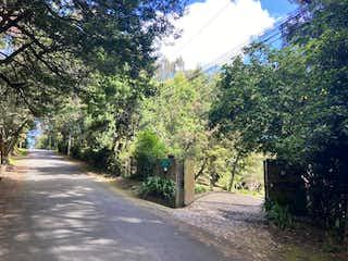 Una calle de la ciudad con un banco y árboles en Casa En Venta En Bogota Altos De Suba