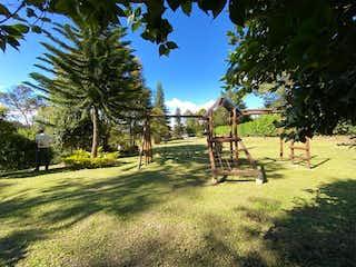 Un par de jirafas que están de pie en la hierba en VENDO FINCA EN RIONEGRO EXCELENTE CASA Y ZONA VERDE