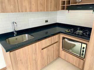 Una cocina con una estufa de fregadero y microondas en VENDO APARTAMENTO, BELLO SANTA ANA