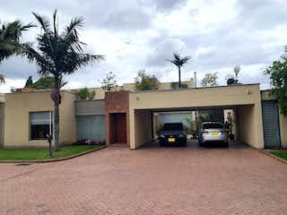 Un par de coches estacionados delante de un edificio en VENTA CASA SAN JOSE DE BAVARIA BOGOT