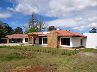 Una casa que está sentada en la hierba en Casa Llanogrande nueva en parcelacion de lujo cabeceras
