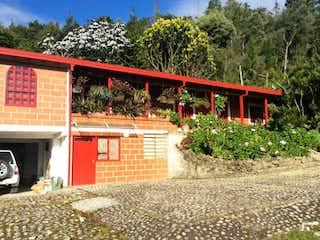 Un edificio de ladrillo rojo con un banco rojo delante de él en Finca tradicional con fonda y 3 Nacimientos con 2 matriculas