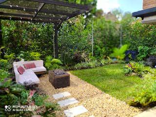 Un banco sentado en medio de un jardín en VENTA HERMOSA CASA SECTOR POBLADO