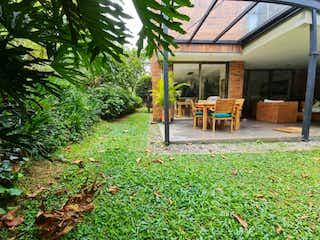 Un banco de madera sentado delante de una casa en Casa  en venta con jardin cerca a El Tesoro