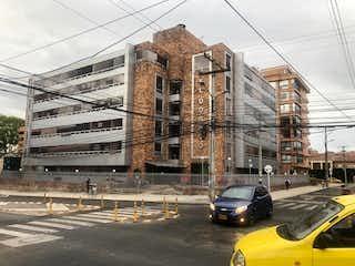 Una calle de la ciudad llena de tráfico al lado de edificios altos en Apartaestudio En Venta En Bogotá Porciuncula