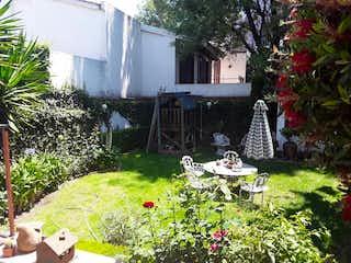 Un jardín con un banco y algunas flores en Venta de Casa en Tlalpan