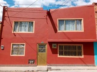 Un edificio de ladrillo rojo con una puerta roja en Casa en venta en Bosa Centro de 6 habitaciones