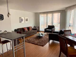 Una sala de estar llena de muebles y una televisión de pantalla plana en Apartamento En Arriendo En Bogota El Nogal