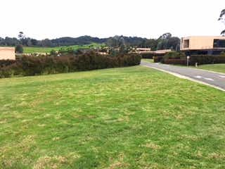 Una vista de un campo de hierba con un edificio en el fondo en Lote en Venta ALTO DE PALMAS
