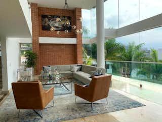 Una sala de estar llena de muebles y un reloj en Venta de casa en El Poblado, Medellín
