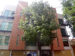 Un edificio alto con un árbol en el fondo en Departamento en venta en Portales de 2 alcoba