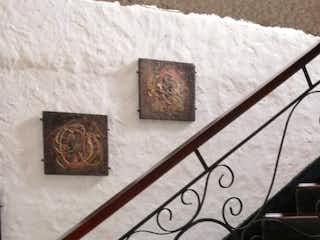 Una habitación con una cama y un reloj en la pared en Casa En Venta En Chia Santa Lucia