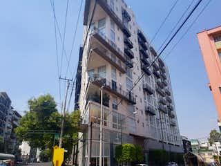 Un edificio alto sentado al lado de una señal de la calle en Departamento en venta en Santa Cruz Atoyac de 2 alcoba