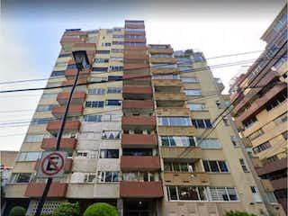 Un edificio alto con una señal en él en Departamento en venta en Insurgentes Mixcoac de 2 alcobas