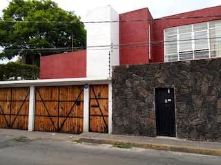 Un edificio de ladrillo rojo con una puerta roja en Casa en Venta en San Juan Tepepan Xochimilco