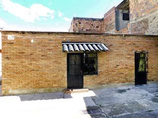 Un edificio de ladrillo con un banco en él en Casa en Venta QUIRIGUA