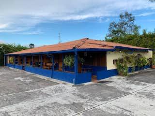 Un autobús azul y blanco estacionado delante de un edificio en Finca llanogrande La Amalita
