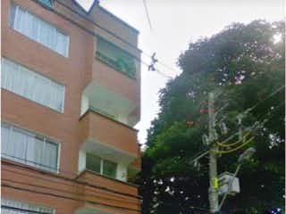 Un edificio alto sentado al lado de un árbol en APARTAMENTO EN MEDELLIN