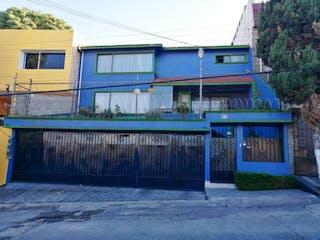 Una casa azul y blanca sentada al lado de un edificio en Casa en Venta en Las Arboledas Atizapán de Zaragoza