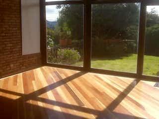 Un banco de madera sentado delante de la ventana en Condominio Campestre Sikasue