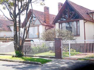 Una casa con un árbol delante de ella en Casa En Venta En Bogota Colina Campestre