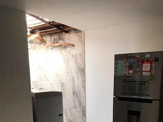 Un refrigerador congelador blanco sentado dentro de una cocina en SE VENDE CASA EN MANRIQUE ESMERALDA