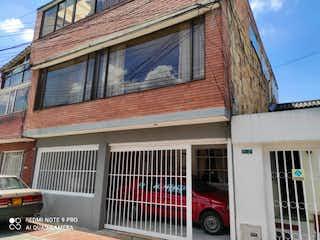 Un edificio de ladrillo rojo con una ventana grande en Casa En Venta En Bogota La Palestina