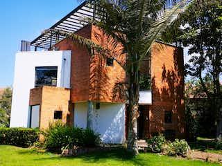 Un edificio de ladrillo con un árbol grande en frente en CASA CAMPESTRE EN CHIA-VENTA