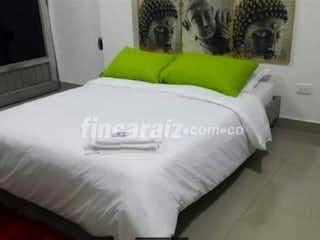 Una cama con un edredón blanco y almohadas en SE VENDE APARTAESTUDIO EN SIMON BOLIVAR