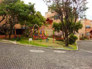 Una calle con un banco de parque y árboles en Casa