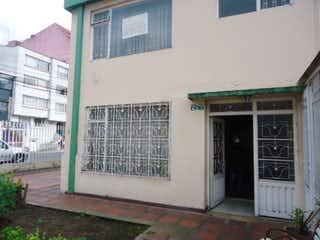 Un edificio blanco con una ventana delante de él en CASA ESQUINERA PARA VENTA