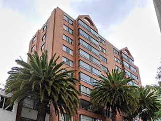Un edificio alto con una palmera delante de él en Vendo Apartamento Chapinero Bogotá