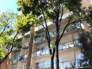 Un árbol delante de un edificio grande en DEPARTAMENTO VENTA COLONIA XOCO