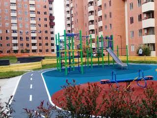 Un gran edificio con un banco de parque al lado en Apartamento en Venta Carrara Zipaquira Cundinamarca