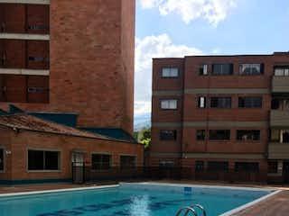 Un edificio azul y blanco con piscina en SE VENDE APTO TRADICIONAL AMPLIO EN LOS COLORES 1 Piso