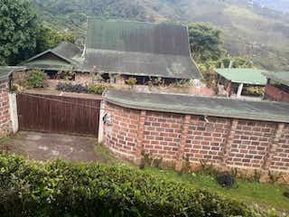 Un edificio de piedra con un banco delante de él en SE VENDE CASA CAMPESTRE SECTOR COPACABANA