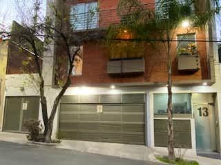 Una casa con un árbol delante de ella en Casa en condominio en San Jerónimo Lídice